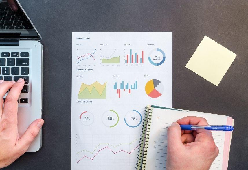 mlabs e dashgoo: imagem de um relatório impresso em cima da mesa, uma mão segurando uma caneta azul escrevendo em um caderno e um notebook ao lado